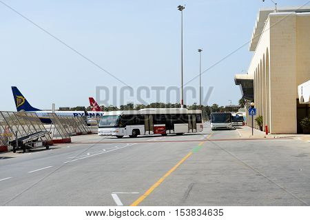 LUQA MALTA - APRIL 18: The bus and building of Malta International Airport on April 18 2015 in Luqa Malta. More then 16 mln tourists is expected to visit Malta in year 2015.