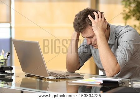 Worried businessman lamenting in front of a computer after a big mistake at office