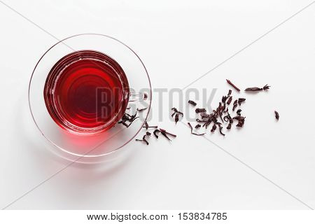 transparent glass cup with Hibiscus tea on the saucer with dry tea leaves on a white background