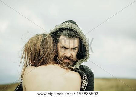 Handsome man hipster with beard and moustache in warm coat and hood hugs undressed girl outdoors on natural background
