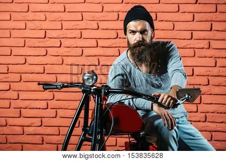 young handsome bearded man hipster or biker with long beard sitting on metallized motorbike or motor cycle on red brick wall background in garage copy space