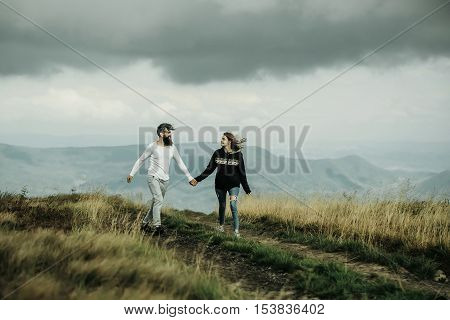 Couple of handsome bearded man in white shirt and pretty young cute girl or woman in black hoody holding hands and bouncing on cloudy sky background
