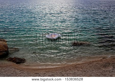 Empty inflatable air bed matrass on blue sea transparent shallow water surface at stony coast on pebble beach