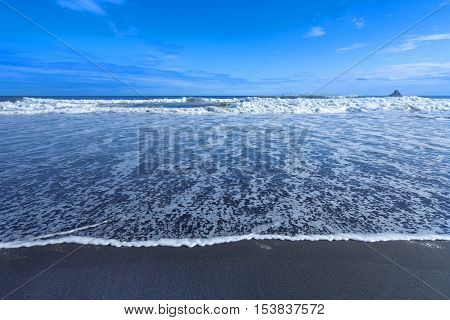 Ocean Beach with blue water and black sand