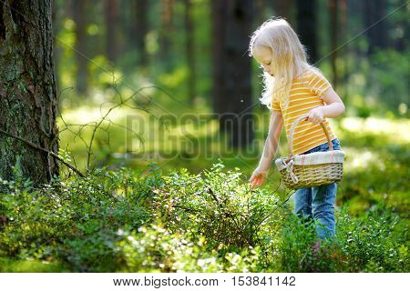 Adorable Little Girl Picking Foxberries In The Forest