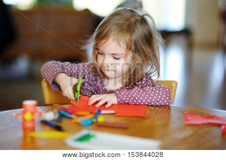 Little preschooler girl cutting colorful paper in preschool