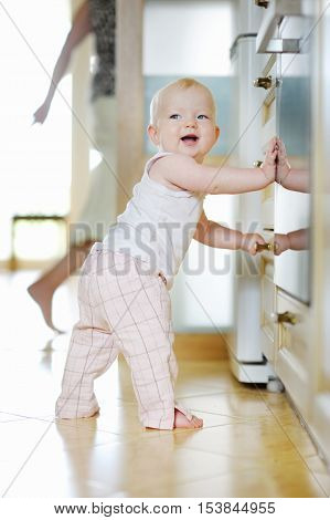 Adorable baby girl plying in kitchen at home