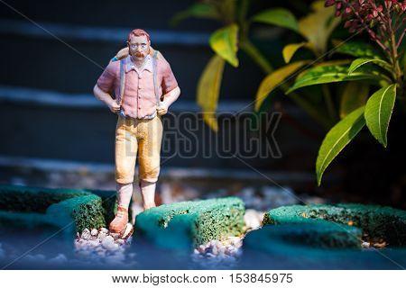 Small hiker figure walking with backback in garden.