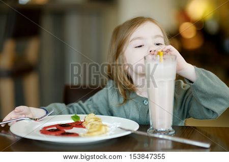 Cute Little Girl Drinking Milk Coctail