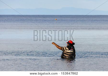 MANA ISLAND, FIJI - AUGUST 20, 2012: Local woman alone in the water fishing on Mana Island Fiji