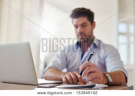 Shot of young businessman at home office with laptop and taking notes. Focus on man hands holding pen.