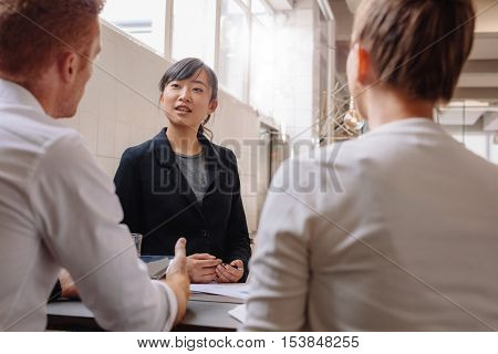 Group of business people having meeting together in modern office. Businesswoman explaining new business ideas to colleagues.