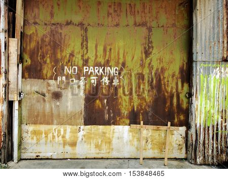 old rusty industrial garage door background. Parking written in english and chinese
