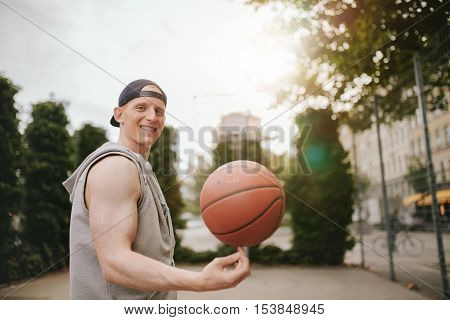 Portrait of smiling streetball player spinning the ball on outdoor court. Happy young man balancing basketball on his finger.