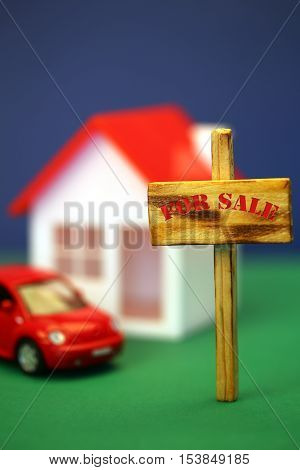 Home for sale sign in front of house model shallow field of focus