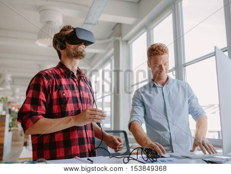 Young developer working on laptop and virtual reality glasses. Two men improving virtual reality glasses in office.