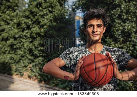 Portrait of young basketball player holding a ball on outdoor court. Teenage guy about to pass the ball. playing streetball.