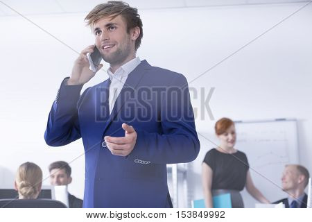 Man In Suit Talking On Phone At Office