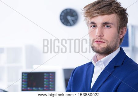 Closer shot of elegant young man standing at modern office