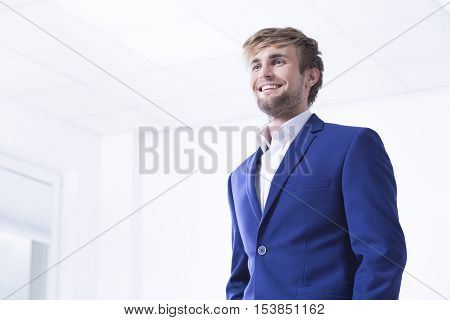 Elegant and handsome young man in bright office interior