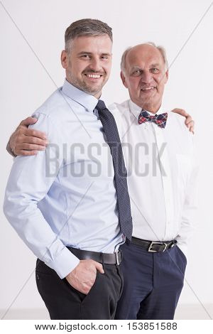 Man and his father standing close each other in elegant clothes