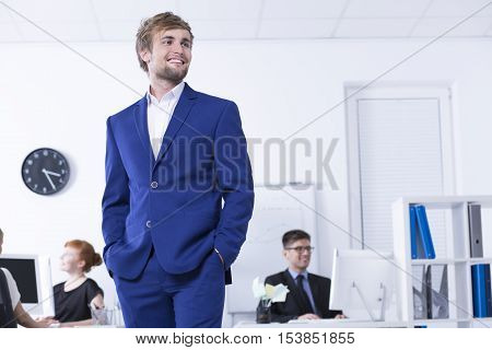 Young man in blue suit standing in the open space office area