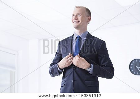 Elegant man in suit standing in bright office area and smiling