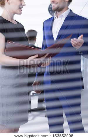 Young woman with documents talking with elegant man in suit at office