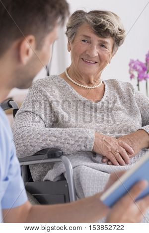 Male Nurse And Elder Woman On A Wheelchair