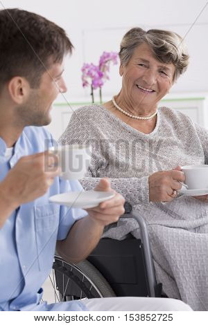 Senior Woman Drinking Tea With Her Caregiver
