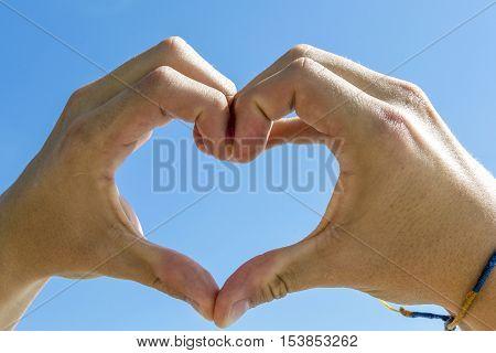Heart Shape With Hand Under Blue Sky