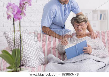Caregiver With Senior Reading A Book