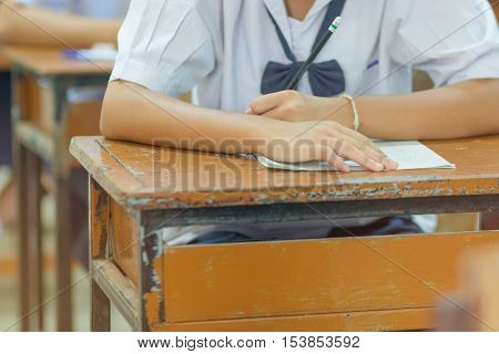 Thai students writing on a paper for Admissions in high school with uniform Thailand