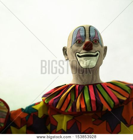 The creepy clown looms in your nightmares - Filtered clown statue at a festival carnival
