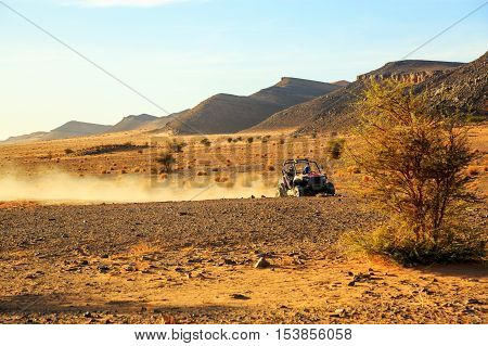 off road car with it's pilot in Morocco desert near Merzouga