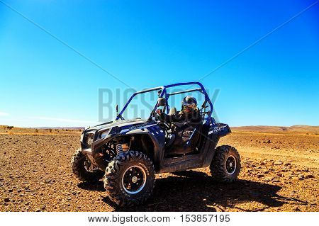 Merzouga Morocco - Feb 23 2016: Front view on blue Polaris RZR 800 with it's pilot in Morocco desert near Merzouga. Merzouga is famous for its dunes the highest in Morocco.