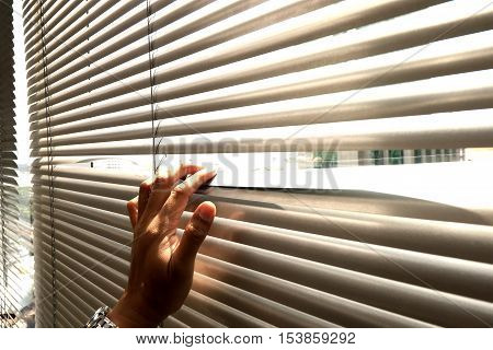 Hand Taking A Peek Through The Window Blinds