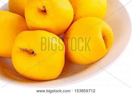 Close-up of a bowl of yellow ripe fruit of the flowering or Japanese quince (Chaenomeles hybrids) isolated against a white background