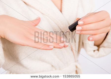 Close up of woman in bathrobe doing manicure and painting nails