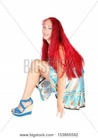 A woman in a dress and heels with long red hair crouching on the floor smiling isolated for white background.