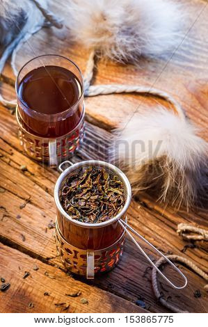 Warming tea served in old-fashioned on old wooden table