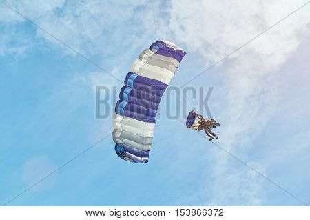 man with blue paraglider isolated on sky