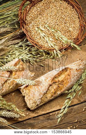 Baguette baked with wholemeal flour on old wooden table
