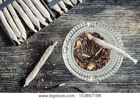 Closeup of cigarettes and ashtray on old wooden table