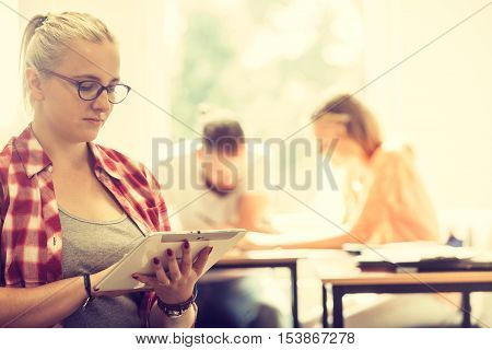 Education high school digital online learning concept - student girl with tablet pc computer sitting in front of students her group mates in classroom