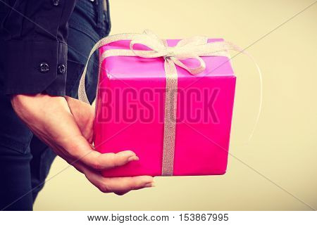 Man hiding pink gift box with ribbon behind back side view. Male hand holding christmas present. Birthday holidays and surprise.