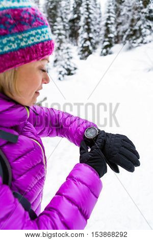 Woman hiker checking the elevation on sports watch smartwatch with altimeter app in winter woods and mountains. Girl trekker in white snowy forest trekking with electronics equipment technology.
