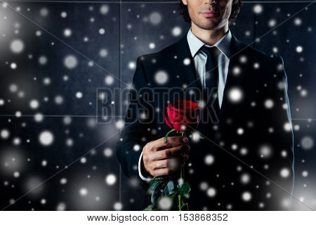 Closeup Photo Of  Man In Formalwear  Holding Red Rose On Snowy Christmas Background