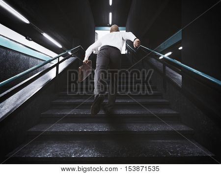 Delayed businessman with bag runs on the stairs