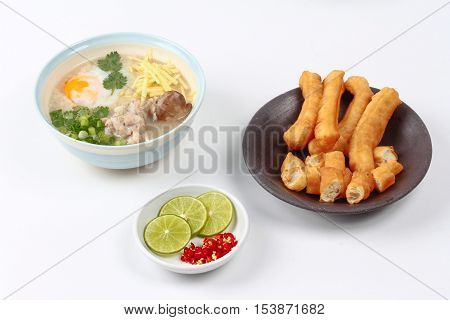 Rice porridge with mined pork and chicken lever served with side dish as Patongko (deep-fried dough stick) and spicy sour fillin.